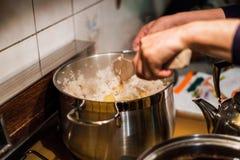Αρχιμάγειρας χεριών που χρησιμοποιεί το ξύλινο βατραχοπέδιλο που αναμιγνύει το ρύζι με την πατάτα στο δοχείο στοκ εικόνες με δικαίωμα ελεύθερης χρήσης