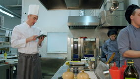 Αρχιμάγειρας χρησιμοποιώντας την ψηφιακή ταμπλέτα και προσέχοντας το εκπαιδευόμενο μαγείρεμά του απόθεμα βίντεο