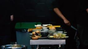 Αρχιμάγειρες που προετοιμάζουν τα πιάτα στην κουζίνα εστιατορίων απόθεμα βίντεο