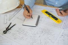 Αρχιτέκτονας ή αρμόδιος για το σχεδιασμό που εργάζεται στα σχέδια για τα σχέδια κατασκευής Στοκ εικόνα με δικαίωμα ελεύθερης χρήσης