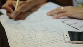 Αρχιτέκτονας γυναικών που εργάζεται με τα φύλλα, τα σχεδιαγράμματα και τα σχέδια σχεδιαγραμμάτων των εγκαταστάσεων Γυναίκα στην ε φιλμ μικρού μήκους