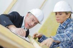 Αρχιτέκτονας και γυναίκες εργαζόμενος που εξετάζουν τα σχεδιαγράμματα Στοκ Εικόνα