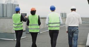 Αρχιτέκτονας και δύο μηχανικοί που περπατούν μέσω του εργοτάξιου οικοδομής στη στέγη και που αναλύουν το σχέδιο αυτοί φθορά φιλμ μικρού μήκους