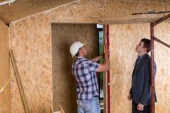 Αρχιτέκτονας και εργαζόμενος που ελέγχουν τα επίπεδα στο πλαίσιο πορτών Στοκ Εικόνα