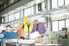 Αρχιτέκτονας και χειρώνακτας που εξετάζουν το σχεδιάγραμμα στον πίνακα στη βιομηχανία στοκ φωτογραφίες