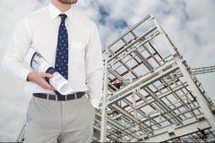 Αρχιτέκτονας με τα σχέδια που στέκονται επάνω στο εργοτάξιο οικοδομής Στοκ φωτογραφία με δικαίωμα ελεύθερης χρήσης