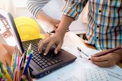 Αρχιτέκτονας με την εργασία συνεργατών με το lap-top στο σχέδιο κατασκευής Στοκ εικόνα με δικαίωμα ελεύθερης χρήσης