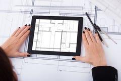 Αρχιτέκτονας με την ψηφιακά ταμπλέτα και το σχεδιάγραμμα Στοκ φωτογραφία με δικαίωμα ελεύθερης χρήσης