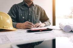 Αρχιτέκτονας που απασχολείται και που εξετάζει στα σχεδιαγράμματα για το νέο πρόγραμμα στο ΝΕ στοκ φωτογραφίες