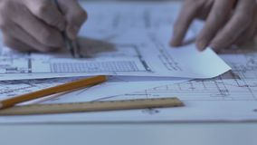 Αρχιτέκτονας που ελέγχει τα σχεδιαγράμματα των κτηρίων, που λειτουργούν στο σχέδιο του κτήματος νέας οικοδόμησης φιλμ μικρού μήκους