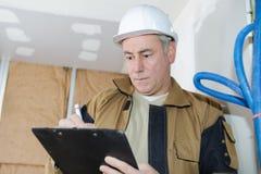 Αρχιτέκτονας που ελέγχει τη μόνωση κατά τη διάρκεια της κατασκευής σπιτιών στοκ εικόνα