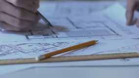 Αρχιτέκτονας που ελέγχει τις οδηγίες οικοδόμησης που σύρουν, γραφείο σχεδίου, κινηματογράφηση σε πρώτο πλάνο χεριών απόθεμα βίντεο
