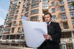 Αρχιτέκτονας που εξετάζει το σχέδιο και το σχεδιάγραμμα διαμερισμάτων Στοκ Εικόνες