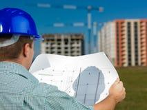 Αρχιτέκτονας που διαβάζει το τεχνικό σχέδιο της κατασκευής Στοκ εικόνα με δικαίωμα ελεύθερης χρήσης
