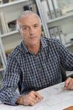 Αρχιτέκτονας που κάθεται στο γραφείο με τις μπλε τυπωμένες ύλες Στοκ εικόνες με δικαίωμα ελεύθερης χρήσης