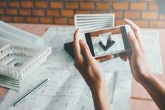Αρχιτέκτονας που χρησιμοποιεί την έξυπνη τηλεφωνική φωτογραφία πρότυπο κτήριο στην αρχή Στοκ φωτογραφία με δικαίωμα ελεύθερης χρήσης
