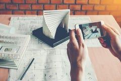 Αρχιτέκτονας που χρησιμοποιεί την έξυπνη τηλεφωνική φωτογραφία πρότυπο κτήριο στην αρχή Στοκ Φωτογραφία
