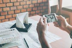 Αρχιτέκτονας που χρησιμοποιεί την έξυπνη τηλεφωνική φωτογραφία πρότυπο κτήριο στην αρχή Στοκ Φωτογραφίες