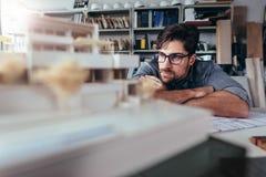 Αρχιτέκτονας στο γραφείο που εξετάζει το πρότυπο σπιτιών Στοκ Φωτογραφίες