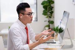 Αρχιτέκτονας στο γραφείο που μιλά στον πελάτη στο τηλέφωνο με τα ακουστικά Στοκ Εικόνα
