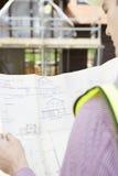 Αρχιτέκτονας στο εργοτάξιο που εξετάζει τα σχέδια για το σπίτι Στοκ Εικόνες