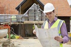 Αρχιτέκτονας στο εργοτάξιο που εξετάζει τα σχέδια σπιτιών Στοκ φωτογραφία με δικαίωμα ελεύθερης χρήσης