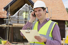 Αρχιτέκτονας στο εργοτάξιο που χρησιμοποιεί το κινητό τηλέφωνο Στοκ Φωτογραφία
