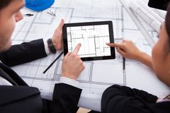Αρχιτέκτονες με την ψηφιακή ταμπλέτα που λειτουργεί στο σχεδιάγραμμα Στοκ Φωτογραφίες
