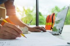 Αρχιτέκτονες που γράφουν τα εγχώρια σχέδια και που χρησιμοποιούν τα lap-top, πρότυπο σπίτι Στοκ Εικόνα