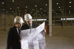 Αρχιτέκτονες που εξετάζουν το σχεδιάγραμμα στην αποθήκη εμπορευμάτων στοκ εικόνες