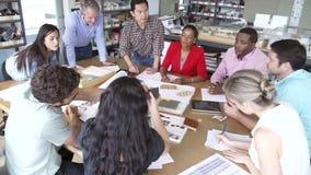 Αρχιτέκτονες που κάθονται τη συνεδρίαση γύρω από τον πίνακα για να συζητήσει τα υλικά απόθεμα βίντεο