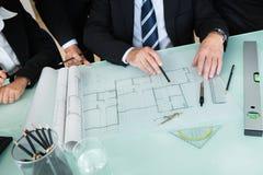 Αρχιτέκτονες που συζητούν ένα σχεδιάγραμμα Στοκ Εικόνες
