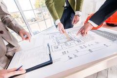 Αρχιτεκτονική απόφαση σχεδίου Τρεις αρχιτέκτονες εξετάζουν Στοκ εικόνες με δικαίωμα ελεύθερης χρήσης