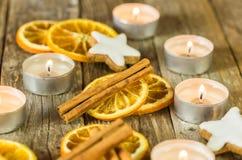 Αρωματική διακόσμηση εποχής Χριστουγέννων με το κάψιμο των κεριών, των μπισκότων αστεριών, της κανέλας και των πορτοκαλιών φετών στοκ εικόνα