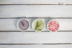 Αρώματα του άλατος λουτρών Αυξήθηκε, lavender και πεύκο κοντά στα κύπελλα με το ζωηρόχρωμο άλας λουτρών στο ελαφρύ ξύλινο αντίγρα στοκ φωτογραφία