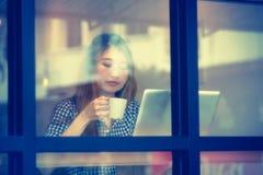 Ασία όμορφη χρησιμοποιώντας το lap-top της και πίνοντας τον καφέ στον καφέ Στοκ φωτογραφία με δικαίωμα ελεύθερης χρήσης