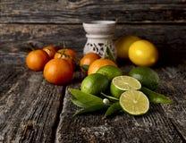 Ασβέστες με τα λεμόνια και tangerines σε ένα ξύλινο υπόβαθρο Ουσιαστικός πετρελαιοκαυστήρας με τα εσπεριδοειδή στοκ εικόνα