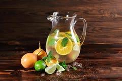Ασβέστης, πορτοκάλι, μέντα - συστατικά για έναν χυμό σε ένα επιτραπέζιο υπόβαθρο Ένα κοκτέιλ με το ρούμι, το ποτό και τα φρούτα δ Στοκ Εικόνες