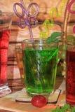Ασβέστης goblets γυαλιού και φρούτα με τη μέντα σε έναν ξύλινο πίνακα στοκ εικόνα