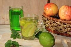 Ασβέστης goblets γυαλιού και φρούτα με τη μέντα σε έναν ξύλινο πίνακα στοκ εικόνες