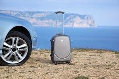Ασημένια βαλίτσα κοντά στο αυτοκίνητο Στοκ φωτογραφία με δικαίωμα ελεύθερης χρήσης