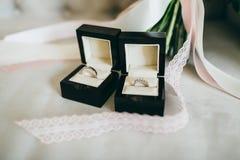 Ασημένια γαμήλια δαχτυλίδια με τους πολύτιμους λίθους όμορφα μαύρα κουτιά στο κομμάτι της κορδέλλας Κινηματογράφηση σε πρώτο πλάν Στοκ φωτογραφία με δικαίωμα ελεύθερης χρήσης