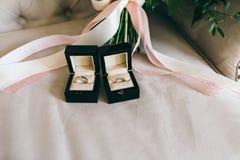 Ασημένια γαμήλια δαχτυλίδια με τους πολύτιμους λίθους όμορφα μαύρα κουτιά στο κομμάτι της κορδέλλας Κινηματογράφηση σε πρώτο πλάν Στοκ εικόνα με δικαίωμα ελεύθερης χρήσης