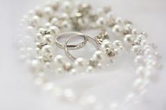 Ασημένια γαμήλια δαχτυλίδια και περιδέραιο μαργαριταριών Στοκ εικόνες με δικαίωμα ελεύθερης χρήσης