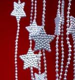 Ασημένια γιρλάντα αστεριών στην κόκκινη ανασκόπηση στοκ εικόνες