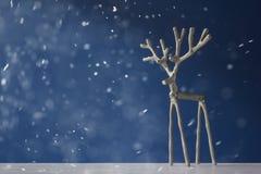 Ασημένια ελάφια αναμνηστικών σε ένα μπλε υπόβαθρο στο χιόνι Στοκ Εικόνες