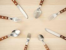 Ασημένια μαχαιροπήρουνα που τίθενται στον ξύλινο πίνακα στοκ εικόνες