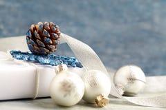 Ασημένια μπιχλιμπίδια Χριστουγέννων, άσπρο παρόν και κορδέλλα σατέν στοκ εικόνες