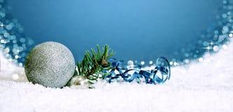 Ασημένια μπιχλιμπίδι και χιόνι Χριστουγέννων στο μπλε Στοκ φωτογραφία με δικαίωμα ελεύθερης χρήσης