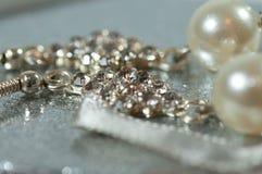 Ασημένια σκουλαρίκια με τους πολύτιμους λίθους και μαργαριτάρια στο λαμπρό κιβώτιο δώρων στοκ εικόνα